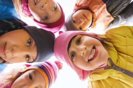 friendship circle: childhood, leisure, friendship and people concept - group of happy children faces in circle Stock Photo