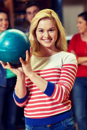 entertainment concept: people, leisure, sport and entertainment concept - happy young woman holding ball in bowling club
