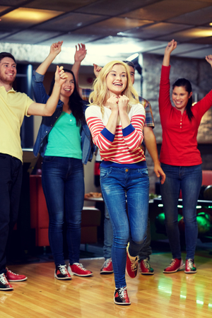 rooting: people, leisure, sport and entertainment concept - happy young woman throwing ball in bowling club