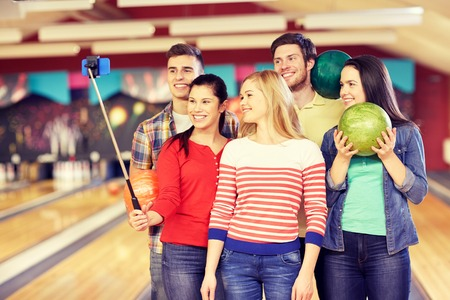 entertainment concept: people, leisure, sport, friendship and entertainment concept - happy friends taking selfie with smartphone on monopod in bowling club