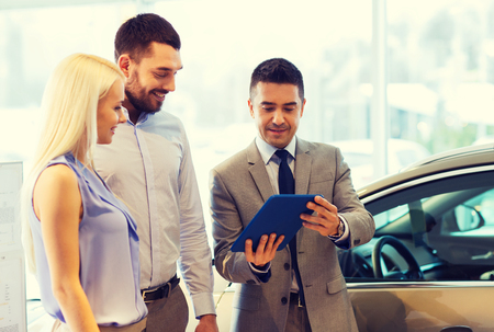 auto: auto business, car sale, technology and people concept - happy couple with car dealer in auto show or salon