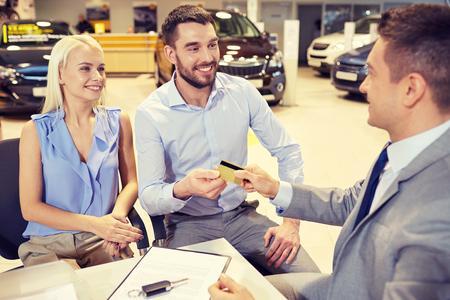 pagando: negocio de los automóviles, la venta y la gente concepto - feliz pareja con distribuidor de comprar coche en salón del automóvil o el salón