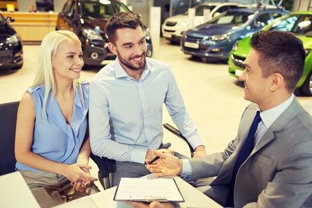autozaken, verkoop en mensen concept - gelukkig paar met dealer kopen auto in autoshow of salon