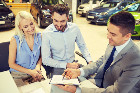 buying a car: auto business, sale and people concept - happy couple with dealer buying car in auto show or salon