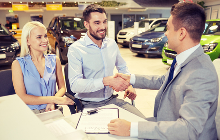 car rent: auto business, car sale, and people concept - happy couple with dealer shaking hands in auto show or salon