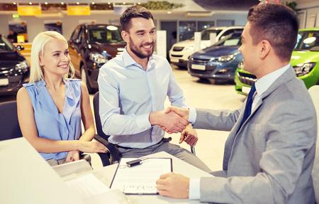settore auto, vendita auto, e la gente il concetto - coppia felice con rivenditori si stringono la mano in auto show o salone