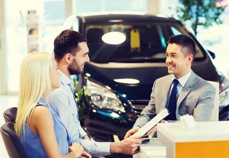 vendedor: negocio de los automóviles, la venta y la gente concepto - feliz pareja con distribuidor de comprar coche en salón del automóvil o el salón