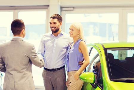buying a car: auto business, car sale and people concept - happy couple with dealer shaking hands in auto show or salon Stock Photo