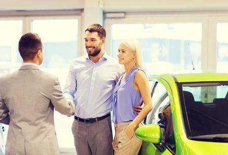 Autogeschäft, Autoverkauf und die Menschen Konzept - glückliche Paare mit Händler Händeschütteln im Auto Show oder Salon