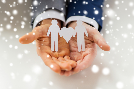 homosexual sex: people, homosexuality, same-sex marriage and love concept - close up of happy male gay couple holding paper cutout love symbol over snow effect Stock Photo
