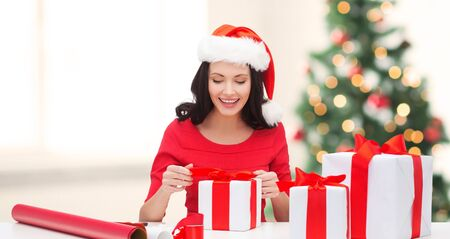 santa helper: christmas, x-mas, winter, happiness concept - smiling woman in santa helper hat with many gift boxes