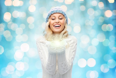 christmas light: winter, magic, christmas and people concept - smiling young woman in winter hat and sweater holding fairy dust on palms over blue holidays lights background Stock Photo