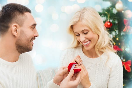proposing: love, christmas, couple, proposal and people concept - happy man giving diamond engagement ring in little red box to woman over blue holidays lights background