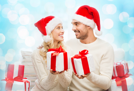 exchanging: christmas, holidays and people concept - happy couple in santa hats exchanging gifts over blue holidays lights background