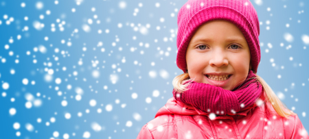 beautiful preteen girl: christmas, winter, childhood, and people concept - happy beautiful little girl portrait over snow background Stock Photo