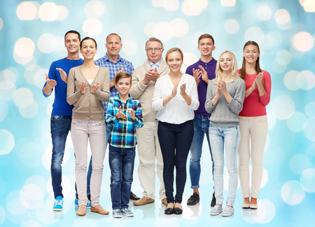 standing together: family, gender, generation and people concept - group of smiling men, women and boy applauding over blue holidays lights background