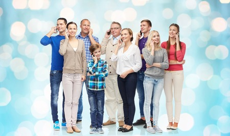 phone calls: family, technology, generation and people concept - group of smiling men, women and boy with smartphones calling over blue holidays lights background Stock Photo
