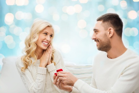 proposing: love, couple, relationship, proposal and holidays concept - happy man giving engagement ring in little red gift box to woman over blue holidays lights background