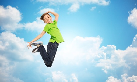 preteen boys: happiness, childhood, freedom, movement and people concept - smiling boy jumping in air over blue sky and clouds background Stock Photo