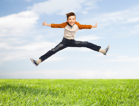 legs spread: happiness, childhood, freedom, movement and people concept - happy smiling boy jumping in air over blue sky and grass background Stock Photo