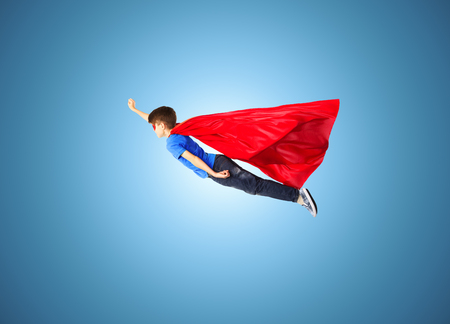 imagination, freedom, childhood, movement and people concept - boy in red superhero cape and mask flying in air over blue background