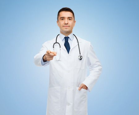 man doctor: healthcare, profession, gesture, people and medicine concept - male doctor in white coat with stethoscope pointing at you over blue background