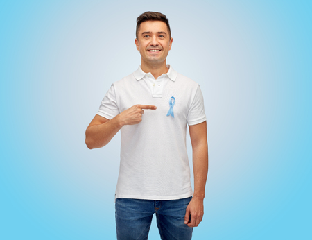 prostate cancer: medicine, health care, gesture and people concept - smiling middle aged latin man in t-shirt with blue prostate cancer awareness ribbon pointing finger on himself
