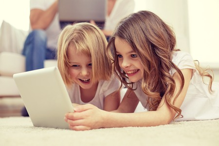 дети: люди, семья, дети, технологии и концепции - счастливые маленькие девочки, играя с планшетного компьютера на дому