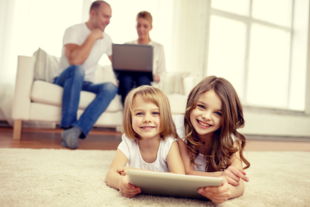 family: people, family, technology and children concept - happy little girls playing with tablet pc computer at home Stock Photo