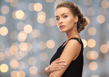happy rich woman: people, holidays and glamour concept - beautiful woman wearing earrings over lights background