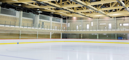 winter, sport, architecture and leisure concept - ice skating rink indoors Banco de Imagens