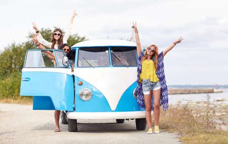 trip over: summer holidays, road trip, vacation, travel and people concept - smiling young hippie friends over minivan car