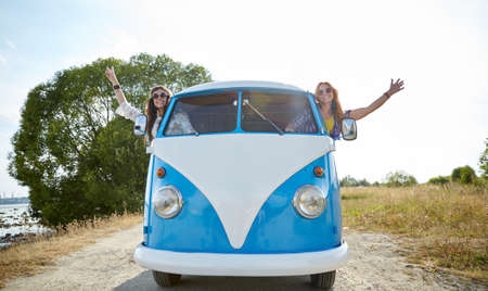hippie woman: summer holidays, road trip, vacation, travel and people concept - smiling young hippie women driving minivan car and showing peace gesture