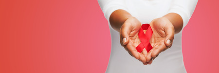 african solidarity: healthcare, people, symbolic and medicine concept - close up of woman hands holding red AIDS awareness ribbon