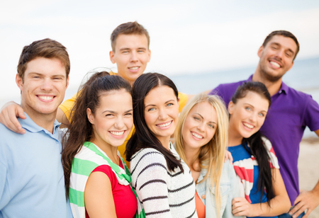 teenage couple: summer holidays, vacation, tourism, travel and people concept - group of happy friends hugging on beach
