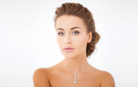 belleza y joyas concepto - mujer que lleva colgante brillante de la diamante