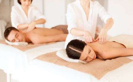 beauty resort: health and beauty, resort and relaxation concept - couple in spa salon getting massage Stock Photo