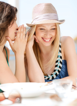 gossiping: summer holidays and vacation concept - girls gossiping in cafe on the beach