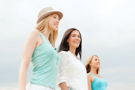 summer holidays and vacation concept - group of smiling girls chilling on the beach Stock Photo
