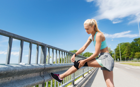 young woman legs up: fitness, sport, exercising and healthy lifestyle concept - young woman with injured leg fastening knee support brace outdoors Stock Photo