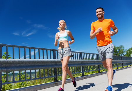 summer sport: fitness, sport, friendship and healthy lifestyle concept - smiling couple running at summer seaside Stock Photo