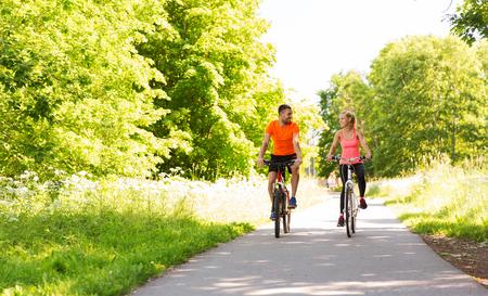 フィットネス、スポーツ、人、健康的なライフ スタイル コンセプト - 夏屋外で幸せなカップルの乗馬の自転車