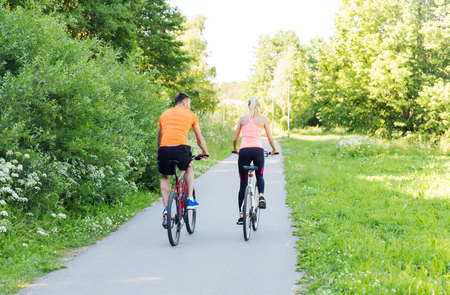 cycler: fitness, sport, people and healthy lifestyle concept - happy couple riding bicycle outdoors at summer from back Stock Photo