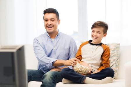 家族、人、技術、テレビ、エンターテイメント コンセプト - 幸せな父と家でテレビを見てポップコーンの息子