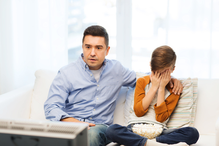 horror: family, people, technology, television and entertainment concept - scared father and son watching horror movie on tv at home