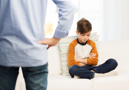 la gente, la mala conducta, la familia y las relaciones de concepto - cerca de un niño culpable malestar o sensación y el padre en el hogar Foto de archivo