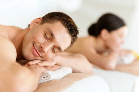 relaxation massage: health and beauty, resort and relaxation concept - couple in spa salon lying on the massage desks