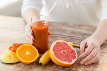 orange juice: healthy eating, food, dieting and people concept - close up of woman hands with fruits and fresh juice sitting at table