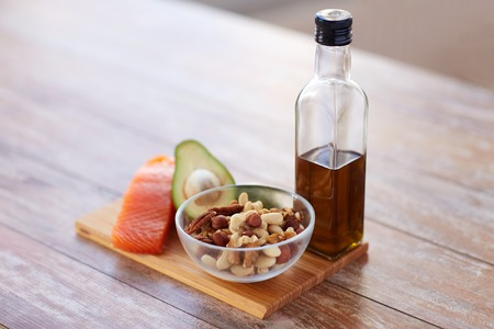 fish: healthy eating, diet and culinary concept - close up of salmon fillets, avocado, olive oil bottle and nuts in glass bowl on table
