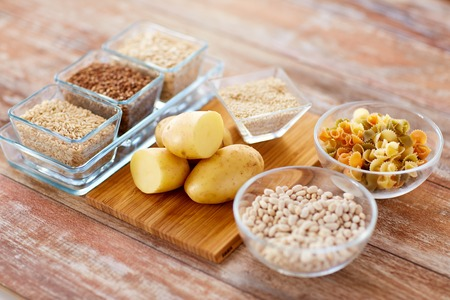 la dieta, el cocinar, culinario y el concepto de alimentos ricos en carbohidratos - Cerca de grano, pasta y frijoles en recipientes de vidrio con las patatas en la mesa